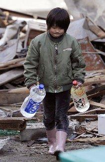 がれきの中で水を運ぶ少年