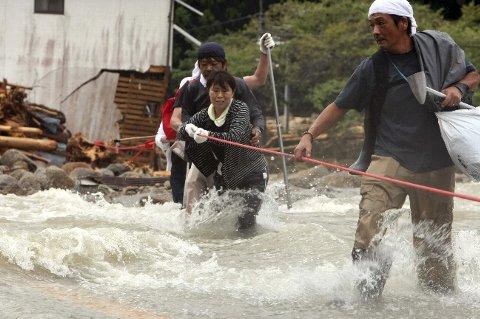 濁流の中、ロープを手に道路を渡る住民たち